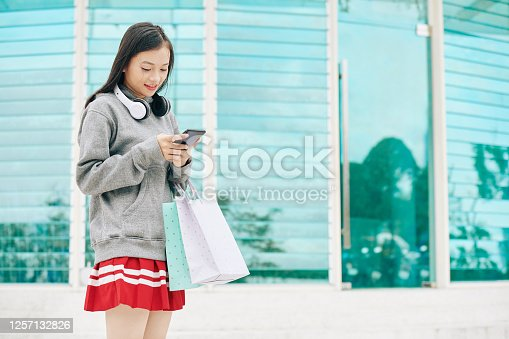 Young Asian woman with shopping bags standing outdoor and checking notifications in her smartphone