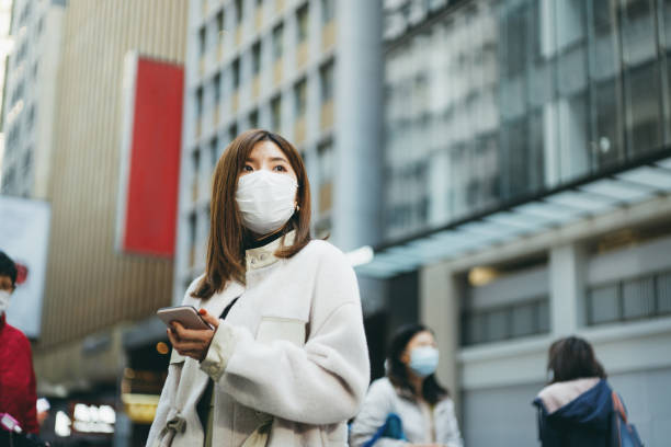 Young Asian woman with smartphone wearing a protective face mask to prevent the spread of germs and viruses in the city