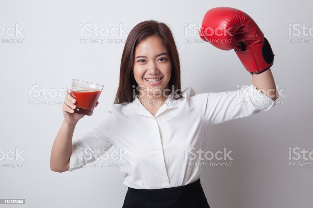 Young Asian woman with tomato juice and boxing glove. foto stock royalty-free