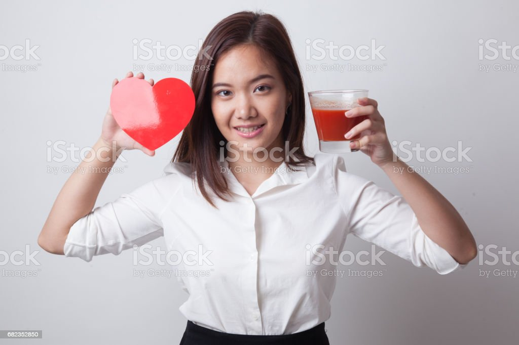 Young Asian woman with tomato juice and red heart. royalty free stockfoto