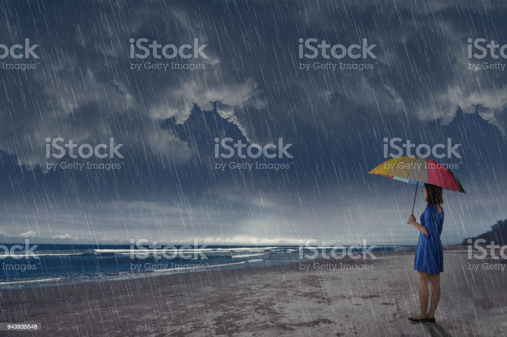 Young asian woman with umbrella looking at ocean view stock photo