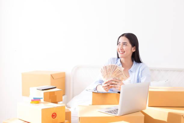 junge asiatische frau zu hause arbeiten, junge besitzer frau beginnen für business online. menschen mit online-shopping kmu-unternehmer oder freiberuflich arbeiten-konzept. - geld schön verpacken stock-fotos und bilder