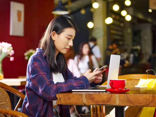 young asian woman working in coffee shop using and cellphone laptop computer - asia orientale foto e immagini stock