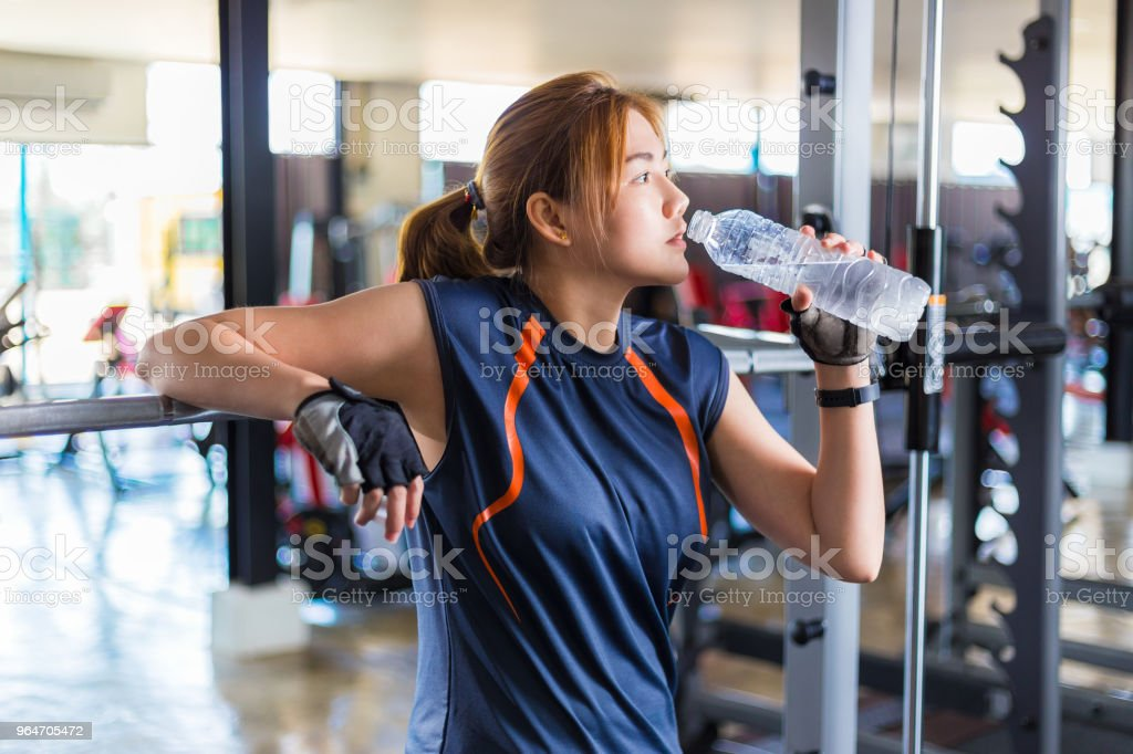 Young Asian woman working out and doing fitness training at a local gym taking a rest to drink water, good for young healthy lifestyle or fitness concept royalty-free stock photo