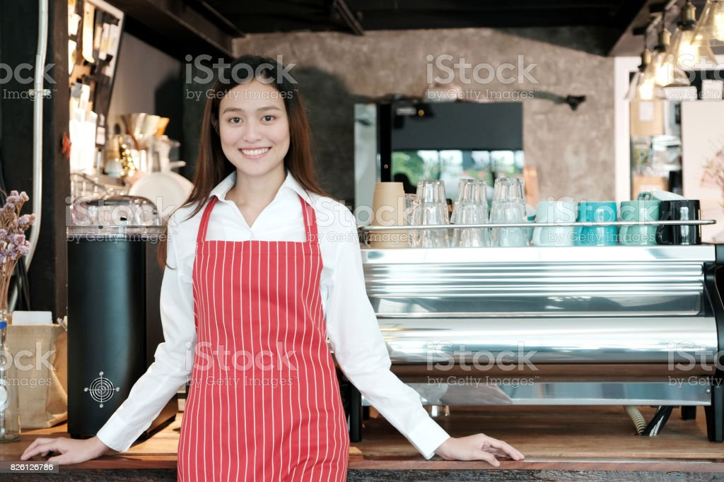 Young asian women Barista standing with smiling face in font of cafe counter background, small business owner, food and drink industry concept stock photo