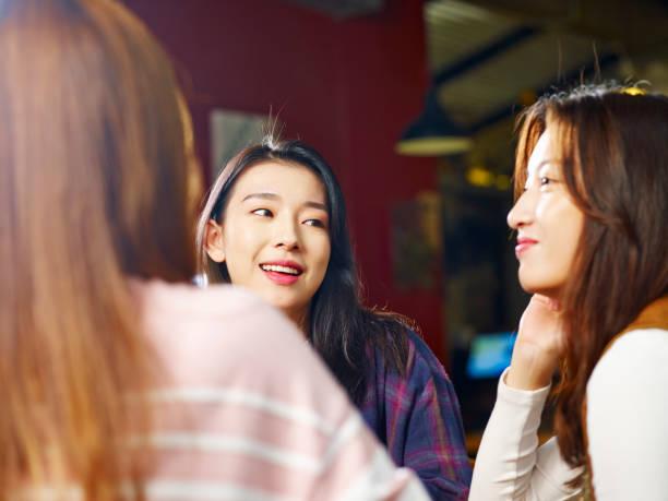 young asian women chatting in coffee shop - asia orientale foto e immagini stock
