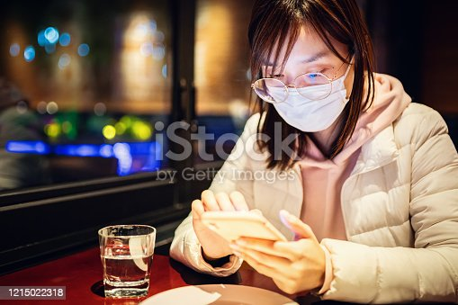 Close up portrait of Asian young woman in the restaurant, she waiting for the dinner with protective face mask and looking at phone, she is searching news of coronavirus.
