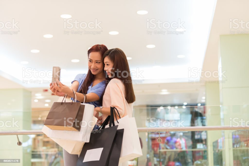 Young Asian Women Friends in Luxury Shopping Mall Taking Selfie stock photo