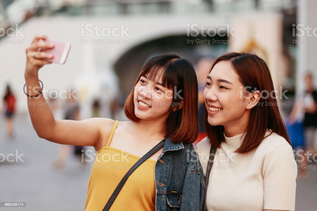 Young Asian women going shopping together in Bangkok, taking a selfie with a phone royalty-free stock photo
