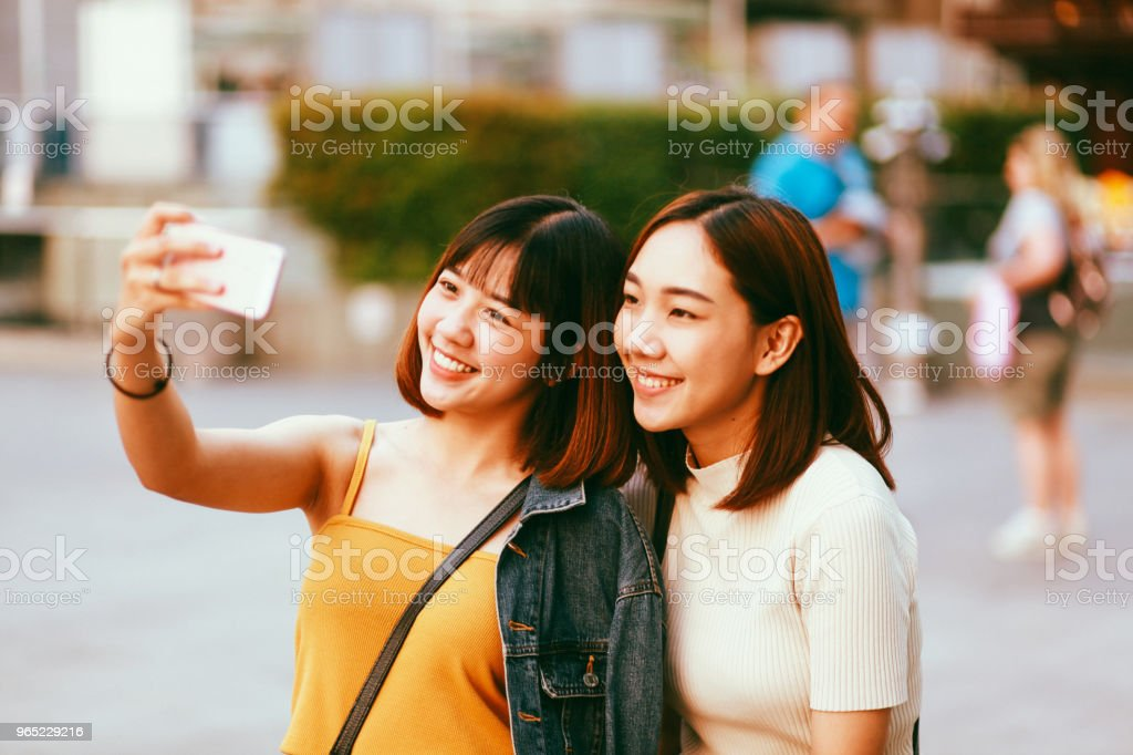 Young Asian women going shopping together in Bangkok, taking a selfie with a phone zbiór zdjęć royalty-free