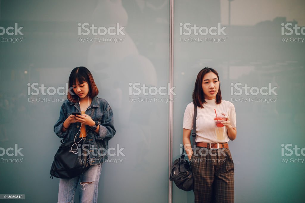 Young Asian women in Bangkok downtown district, taking a break, texting on the cellphone, waiting stock photo