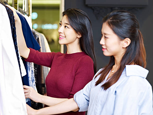 young asian women in clothing store - 小売販売員 ストックフォトと画像