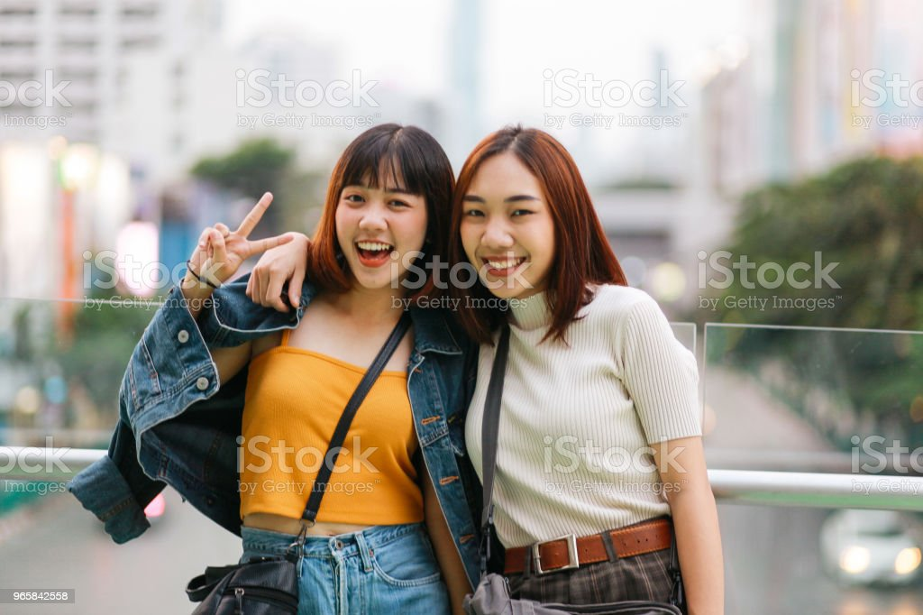 Young Asian women posing in Bangkok, going shopping together, having fun Vintage toned image of two young, Asian women, walking together, chatting, going shopping near Siam station on Bangkok Sukhumvit line. They're wearing casual street style clothing, enjoying an afternoon together. Adult Stock Photo