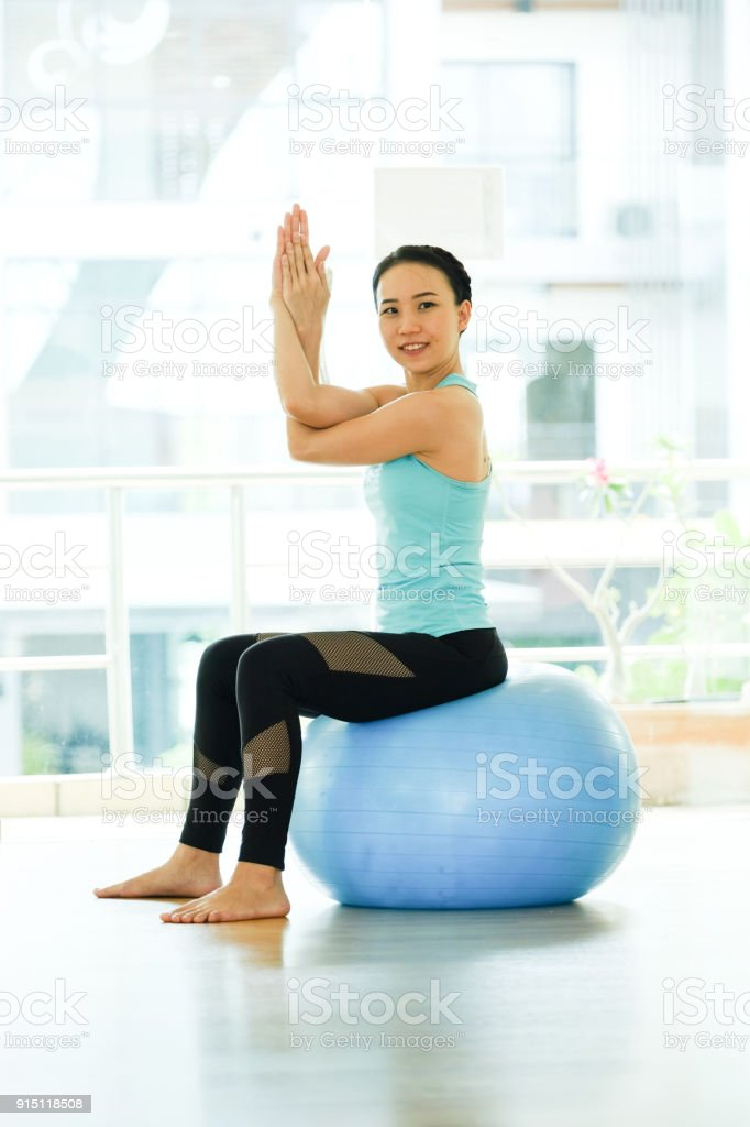 Young asian women practicing yoga ball, fitness stretching flexibility pose, working out, healthy lifestyle, wellness, well being stock photo