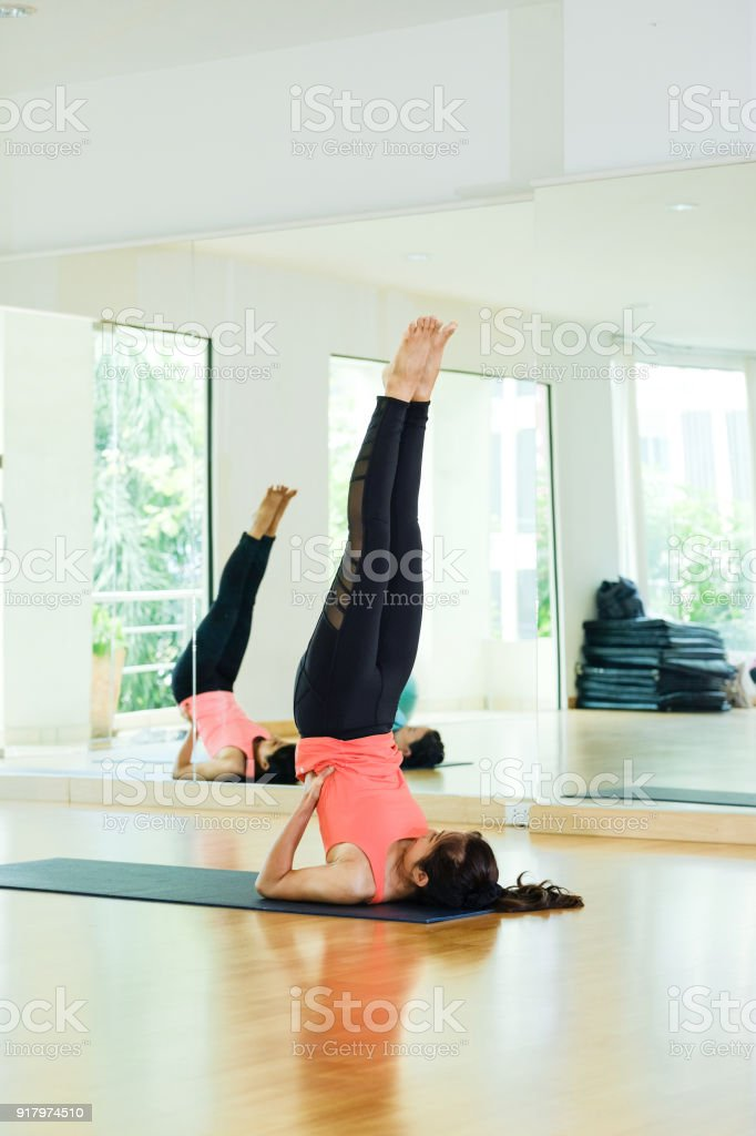 Young asian women practicing yoga, fitness stretching flexibility pose, working out, healthy lifestyle, wellness, well being stock photo