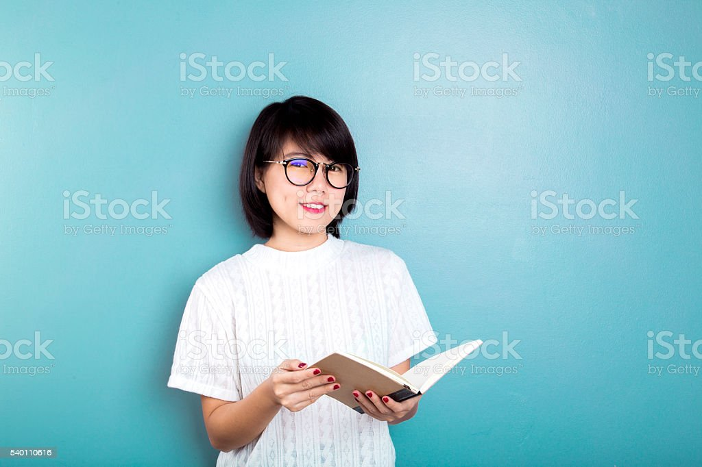 Young asian women thinking on blue background. stock photo