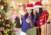 クリスマスの買い物中に携帯電話を使用して若いアジアの女性