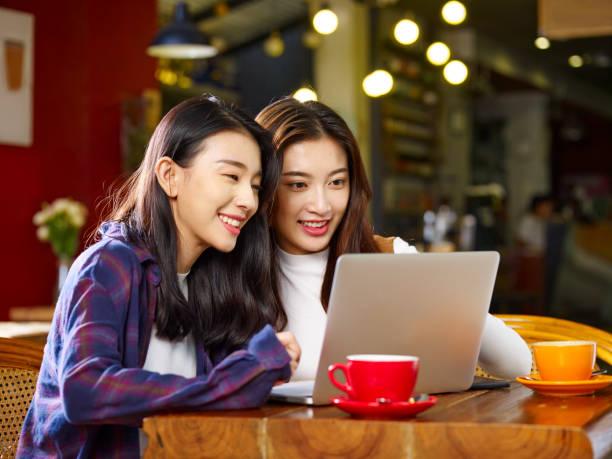 コーヒー ショップでノート パソコンを使用して若いアジア女性 - 同性カップル ストックフォトと画像