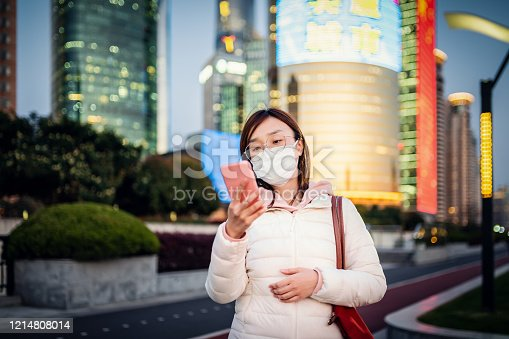 Close up portrait of Asian young woman on the street, she walking on the street with protective face mask and looking at phone, she is searching news of coronavirus.