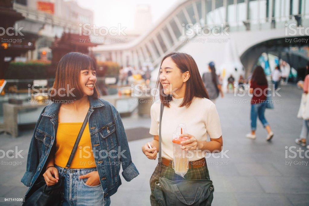 Young Asian women walking in Bangkok, going shopping together, chatting