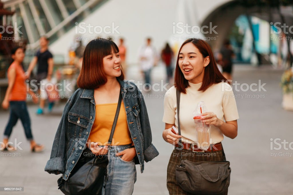 Young Asian women walking in Bangkok, going shopping together, chatting royalty-free stock photo
