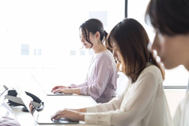 若いアジアの女性は、オフィスで働きます。 - パソコン 日本人 ストックフォトと画像