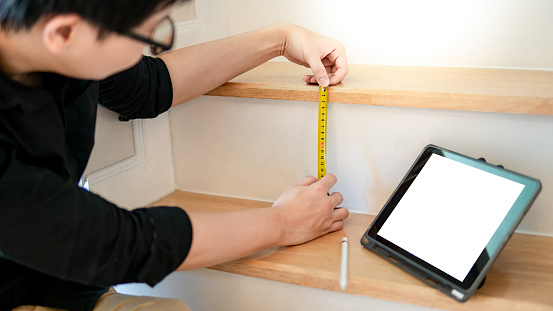 1167393641 istock photo Young Asian worker using tape measure for measuring riser and thread on stair in the house. Writing note and sketching on digital tablet for design information. Housing construction and renovation 1073162664