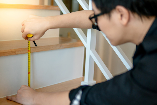 1167393641 istock photo Young Asian worker using tape measure for measuring riser and thread on stair in the house. Housing staircase construction and renovation. 1133497848