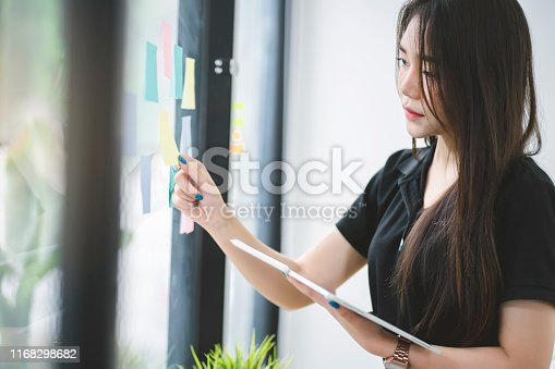 858413274 istock photo Young Asian working woman putting sticky note paper reminder on the glass wall. 1168298682