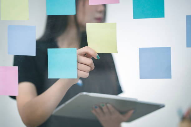 Young Asian working woman putting sticky note paper reminder on the glass wall. stock photo