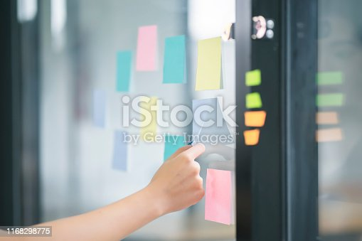 858413274 istock photo Young Asian working woman putting sticky note paper reminder on the glass wall. 1168298775
