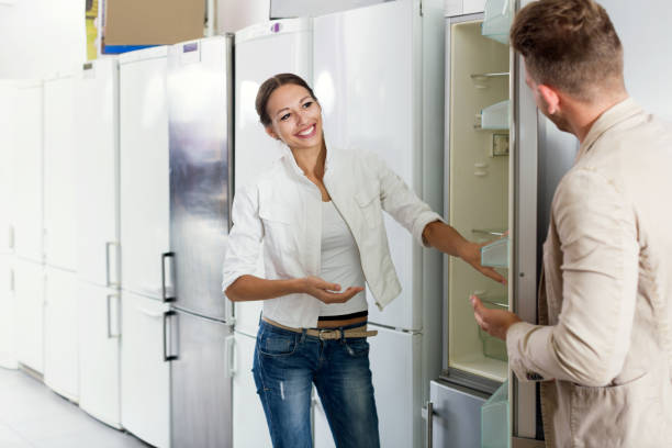 young assistant in the shop sell a fridge - happy person buy appliances stock photos and pictures