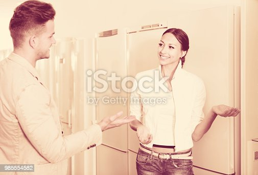 876810414istockphoto Young assistant in the shop sell a fridge 985554582