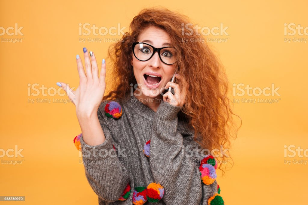 Young astonished woman with red hair talking on mobile phone stock photo