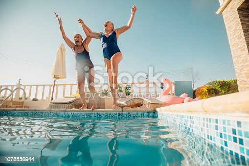 Two senior women holding hands and jumping into a swimming pool. They're excited and having fun.
