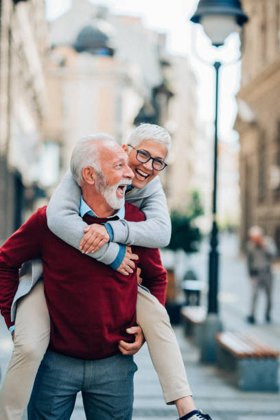 Young at heart Happy senior couple piggyback ride outdoor in the city piggyback stock pictures, royalty-free photos & images