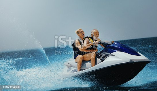 Senior couple enjoying jet skiing on their summer vacation.