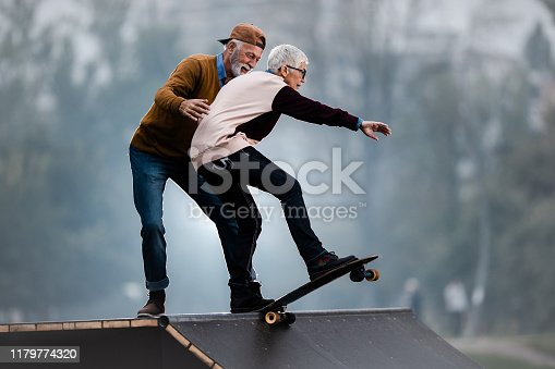 Senior woman riding skateboard on a ramp while her husband is assisting her in a skate park.