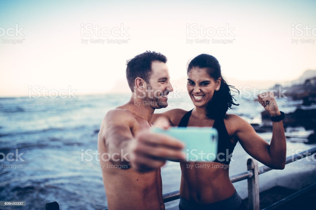young athlete couple taking selfie with smartphone stock photo