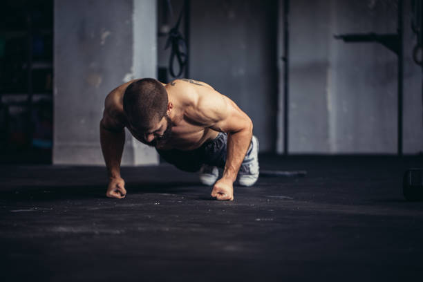 young athlete doing push-ups - push up stock photos and pictures