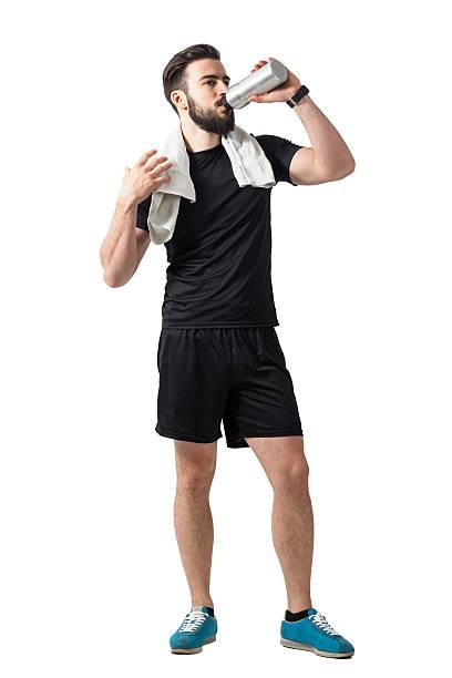 Jeune athlète boire un verre smoothie de bouteille avec la serviette autour du cou - Photo