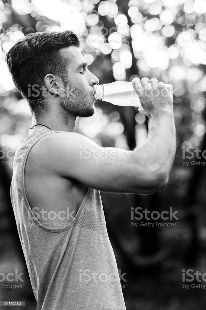 Young athlete drinking water in park.black and white photo stock photo