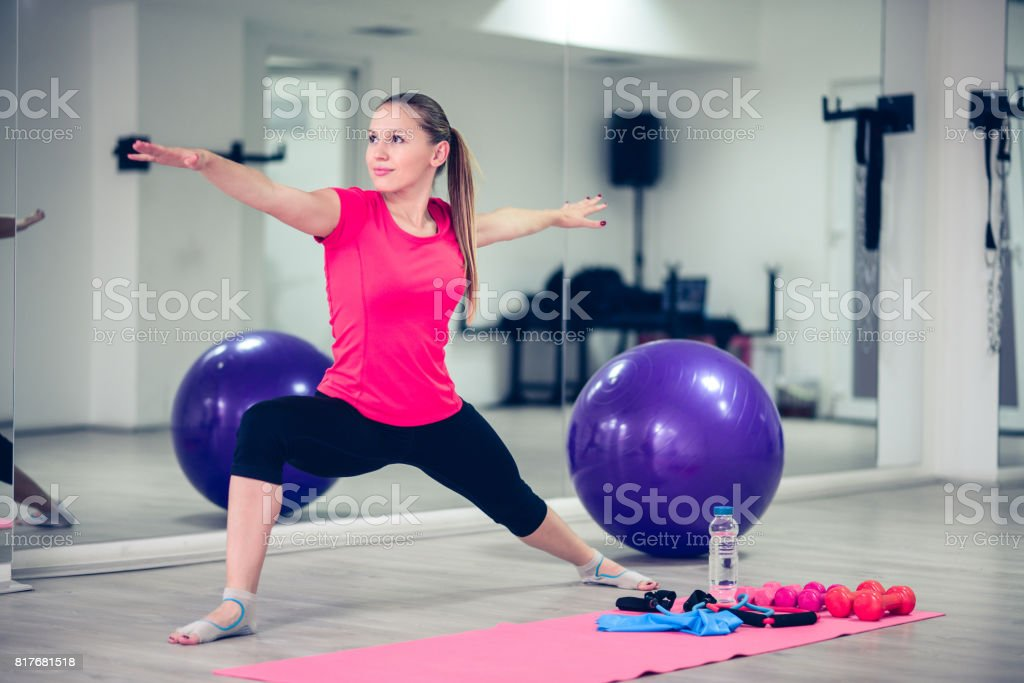 Young Athlete Female Practising Pilates In Front of Gym Mirror stock photo
