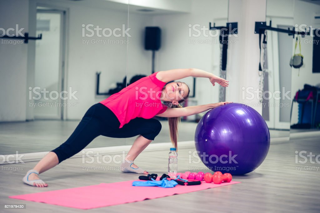Young Athlete Female Practising Yoga Pilates In Front of Gym Mirror stock photo