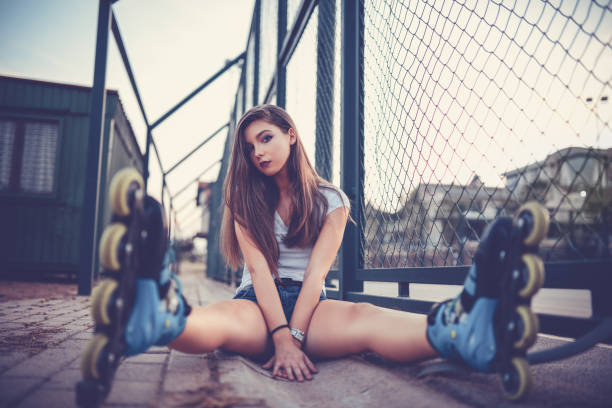 joven atleta rollerblader mujer sentada y posando en el skate park - piernas abiertas mujer fotografías e imágenes de stock