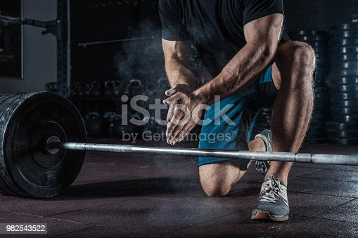944655208 istock photo Young athlete getting ready for weight lifting training. 982543522