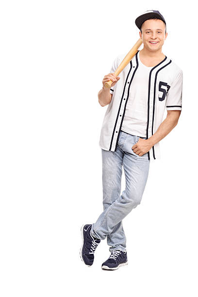 Young athlete holding baseball bat and leaning on a wall stock photo