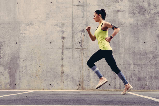 Young athlete jogging outside Sportswoman training outside for slim body cardiovascular exercise stock pictures, royalty-free photos & images