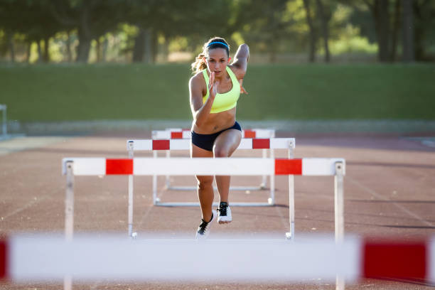 young athlete jumping over a hurdle during training on race track. - corsa su pista femminile foto e immagini stock