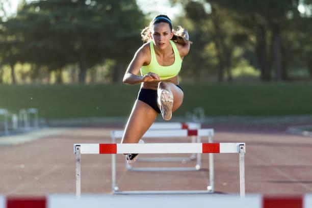 Junge Athleten springen beim Training auf Rennstrecke über eine Hürde – Foto
